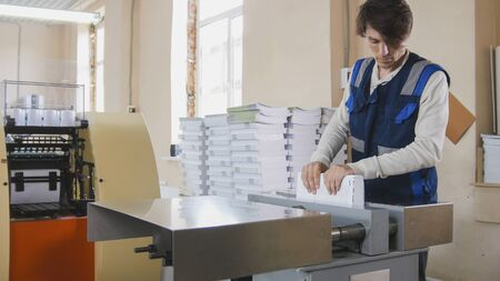 The print operator checks the quality of the finished product Stock Photo