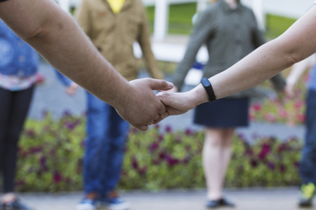 A lot of people holds hands in park - dancing performance Stock Photo