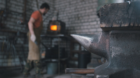 forge: Muskular man - blacksmith in forge near furnace