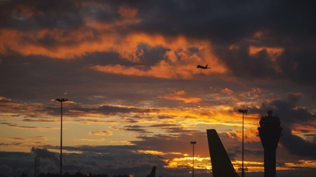 The aircraft takes off into a cloudy sunset sky
