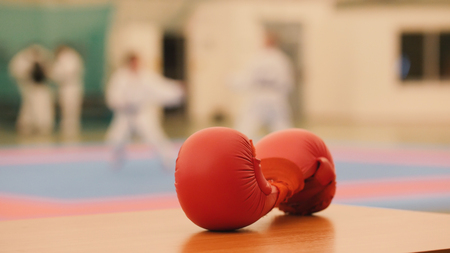 Red karate gloves on tatami during training, de-focused