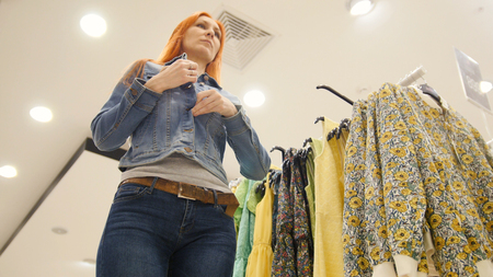 Girl chooses a jeans jacket, shopping for women Stock Photo
