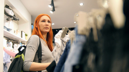 Girl chooses dress in clothing store or mall, woman among dresses