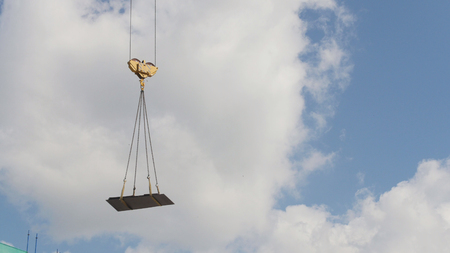 A crane lifting heavy equipments on a construction site - in front of blue sky