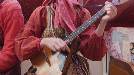 Folk music russian ensemble - woman in Russian folk costume playing the balalaika