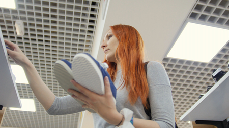 luxury room: Attractive red haired woman chooses a sneakers in shoes store - shopping concept Stock Photo
