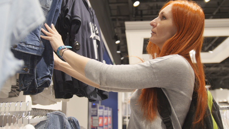 hangers: Yong positive woman is choosing a dress in womens clothing store