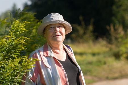Happy grandma - senior woman in white hat smiling in the park or garden