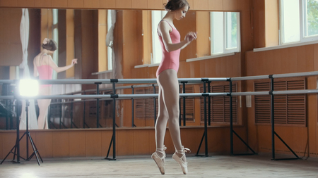 woman mirror: A young girl gracefully performs acrobatics tricks in studio