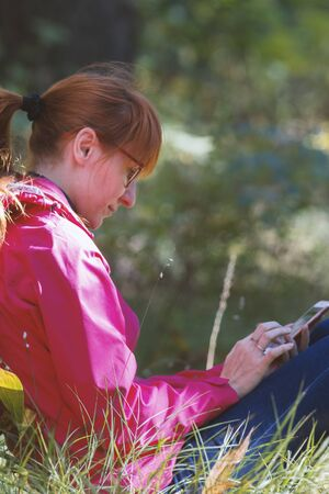 Young woman in pink jacket uses smartphone in the autumn forest - vertical