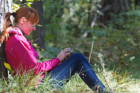 Young woman in pink jacket uses smartphone in the autumn forest - horizontal