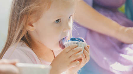 Cute blonde girl eating cupcake outdoor with family
