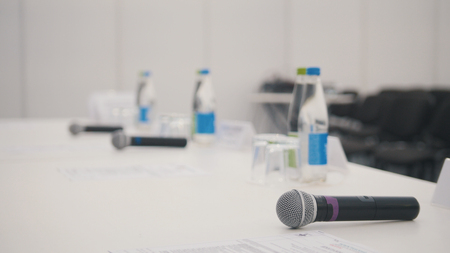 Table at conference - microphones - in auditorium waiting for performances, close up