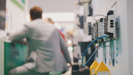 People working in high-tech industry room near electronic equipment Stock Photo