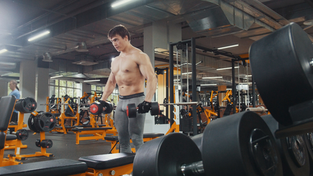 Athlete man lifting dumbbells without shirt in the gym Banco de Imagens