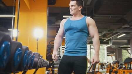 Bodybuilding in the gym - young muscular sporty man have rest after training