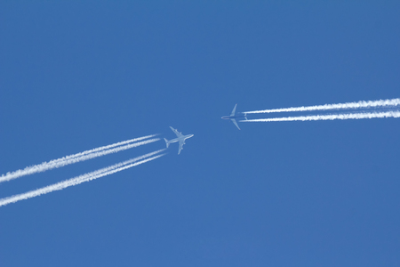 Two passengers airplanes are flying to each other in blue sky