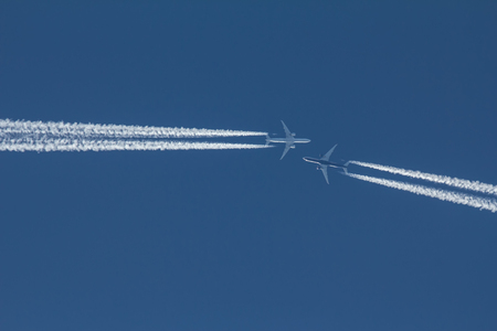 Two passengers jets are flying to each other in blue sky