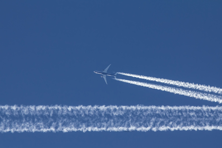Passengers jet is flying in perfect blue sky Stock Photo
