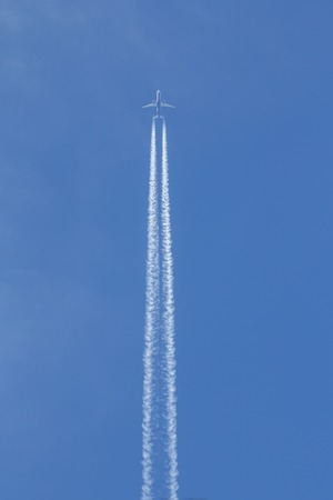 Jet is flying in the blue sky, vertical