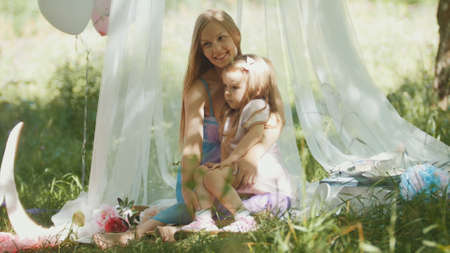 Mother and daughter hugging in park - picnic and birthday