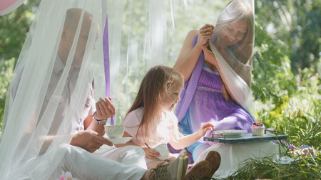 Portrait of cute blonde little girl with family in park Stock Photo