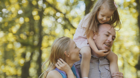 Father, mother and daughter having fun in park at sunny day Stock Photo