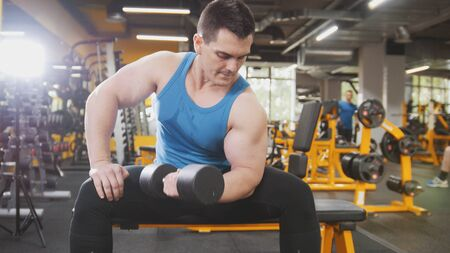 Bodybuilding in the gym - young sporty man performs training for arm