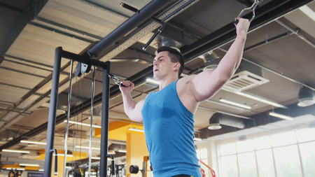 Bodybuilder training in the gym - young muscular man perform training for biceps, slider shot Stock Photo