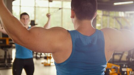 barbel: Bodybuilder training in the gym - young muscular man perform training for biceps near mirror