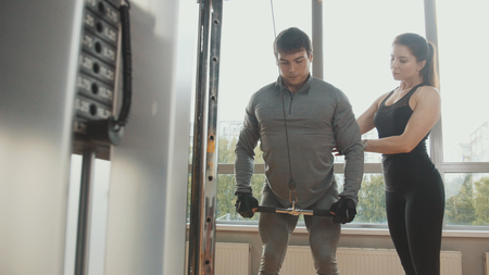 Athlete man performs exercises in the gym