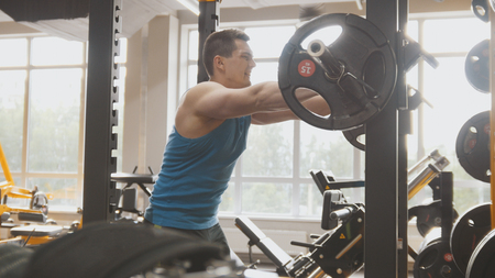 Fitness gym - muscular man performs squats with barbell Stock Photo