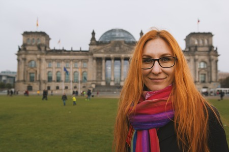 Red hair young woman near the Reichstag building german government in Berlin, Germany