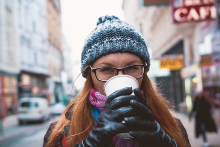 Young stylish woman drinking coffee to go in a city street of autumn vienna Stock Photo