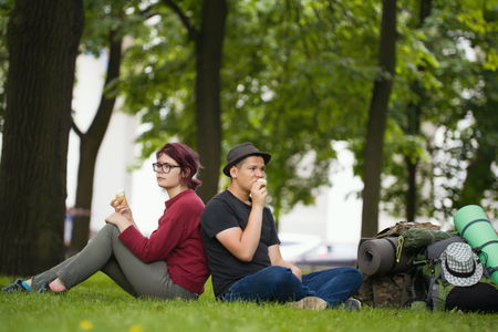 Young couple tourists with backpacks are eating the icecream in the park Stock Photo