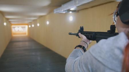 Mujer disparando con una ametralladora en la galería de tiro