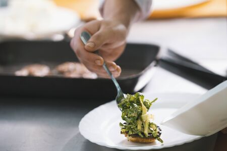 Chef serves dish on the plate in restaurant Stock Photo