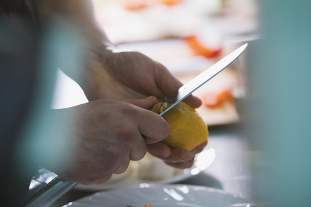 Chef is peeling potatoes for salad in commercial kitchen