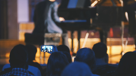 Spectators at concert of classic misic - people shooting performance on smartphone, scottish musicians Stock Photo