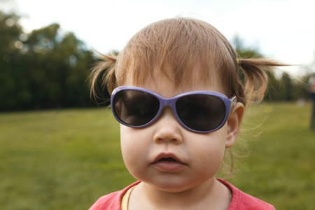Cute Little toddler girl in sunglasses in park in front of green grass