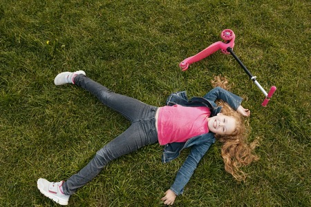 Smiling child girl wearing jeans jacket lying on green grass with pink scooter