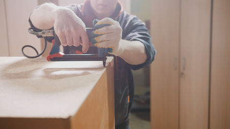Carpenter working with an electric industrial stapler on the factory, fixing furniture details, industry