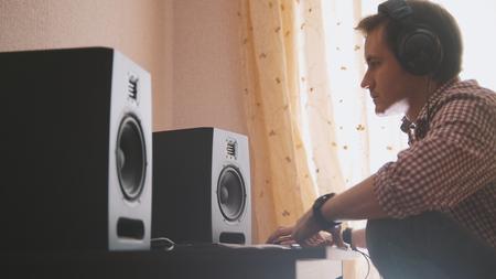 若い男の作曲家は、コンピュータ上の音楽を作曲し、サウンドエンジニアが働く 写真素材