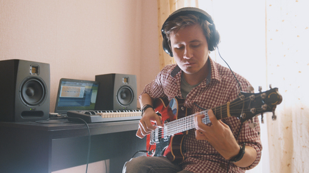 Young musician composes and records music playing the guitar using computer