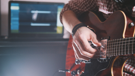 Young musician composes and records soundtrack playing the guitar, using computer and keyboard, from the front view Stock Photo