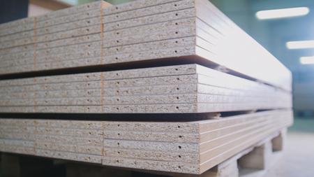 Stapel houten spaanplaatpanelen op het pakhuis of de fabriek