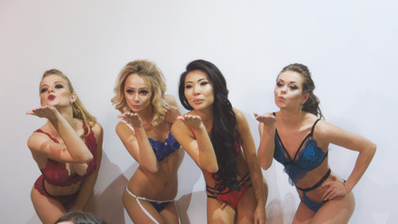 Four young women in underwear makes air kiss