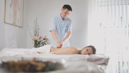 Doctor osteopat and patient - young woman lying on massage table - medical treatment Imagens