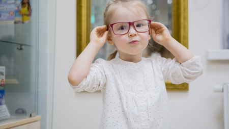 Little girl tries fashion medical glasses near mirror - shopping in ophthalmology clinic 版權商用圖片