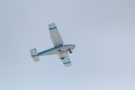 Small sports plane flying in the cloudy sky